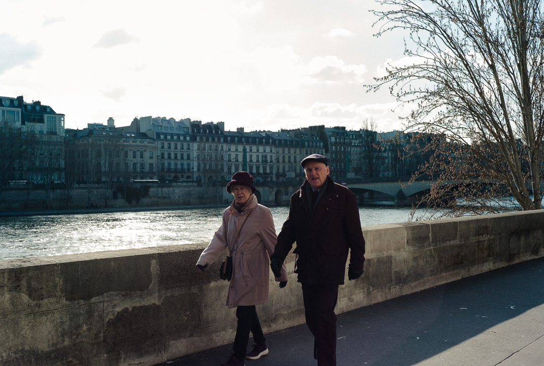 Old couple walking along the Seine River
